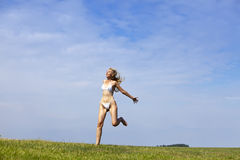 The happy woman in white bikini  jumps in a summer green field against the blue sky Stock Images