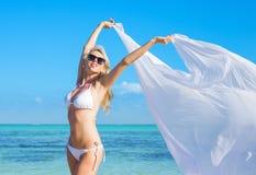 Happy woman in white bikini relaxing on the beach Stock Image