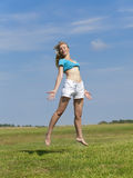 The happy woman in white bikini and shorts jumps in a summer green field against the blue sky Royalty Free Stock Photography