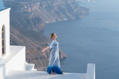 Happy woman in white and blue dress enjoying her holidays on Santorini, Greece. View on Caldera and Aegean sea from. Imerovigli. Active, travel, tourist royalty free stock photo