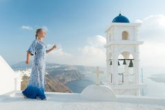 Happy woman in white and blue dress enjoying her holidays on Santorini, Greece. View on Caldera and Aegean sea from. Imerovigli. Active, travel, tourist stock image