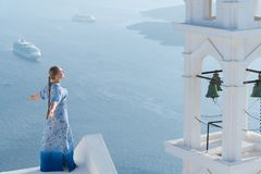 Happy woman in white and blue dress enjoying her holidays on Santorini, Greece. View on Caldera and Aegean sea from. Imerovigli. Active, travel, tourist royalty free stock image