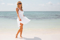 Happy woman in white dress enjoying vacation on tropical beach Royalty Free Stock Photography