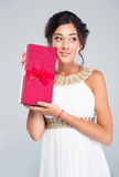 Happy woman in white dress holding gift box. And looking away over gray background Stock Images