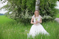 Happy woman in white dress leaning on a birch tree Royalty Free Stock Photo