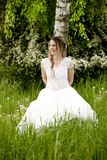 Happy woman in white dress leaning on a birch tree Stock Images