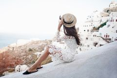 Woman in white dress and straw hat on Santorini island. Happy woman in white dress and straw hat enjoying her holidays on Santorini island. View on Aegean sea Royalty Free Stock Photography