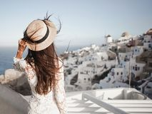 Woman in white dress and straw hat on Santorini island. Happy woman in white dress and straw hat enjoying her holidays on Santorini island. View on Aegean sea Royalty Free Stock Photo