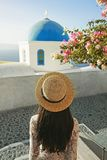 Woman in white dress and straw hat on Santorini island. Happy woman in white dress and straw hat enjoying her holidays on Santorini island. View on Aegean sea Royalty Free Stock Photos