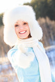 Happy woman in white fur hat Stock Photography