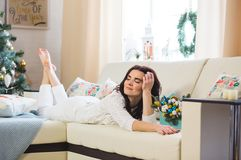 Happy woman in white knitted wearing relax at home for Christmas royalty free stock photos