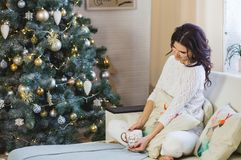 Happy woman in white knitted wearing relax at home for Christmas stock photography