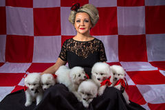 Happy woman with white little puppies Royalty Free Stock Image