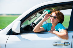 Happy woman in white new car at nature Royalty Free Stock Image