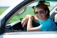 Happy woman in white new car at nature Stock Photography