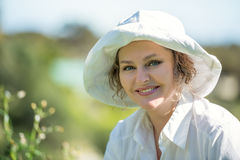 Happy woman in white  outdoors. Happy woman in white hat and shirt is smiling outdoors Royalty Free Stock Photos