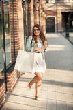 Happy woman with white paper bag at shopping mall Royalty Free Stock Photos