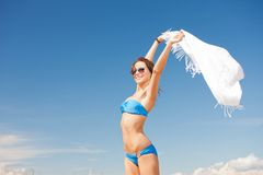Happy woman with white sarong on the beach Stock Images