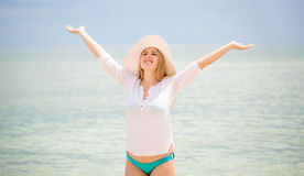 Happy woman in white shirt and hat stretching at sea Royalty Free Stock Images