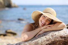 Happy woman with white smile looking sideways on vacations. With the beach in the background royalty free stock photo