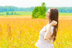 Happy woman in a white sundress in the field Stock Photography