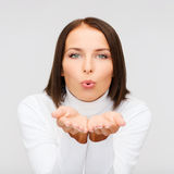 Happy woman in white sweater blowing on palms Royalty Free Stock Images