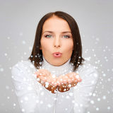 Happy woman in white sweater blowing on palms Royalty Free Stock Image