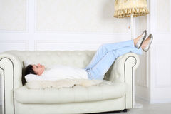 Happy woman in white sweater and jeans lies on sofa royalty free stock images