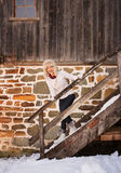 Happy woman in white sweater on stairs of cosy mountain house Royalty Free Stock Images