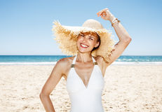Happy woman in white swimsuit and straw hat at sandy beach Stock Photo