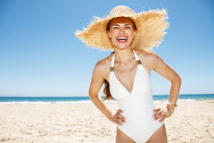 Happy woman in white swimsuit and straw hat at sandy beach Royalty Free Stock Photography