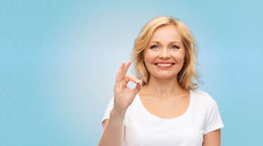 Happy woman in white t-shirt showing ok hand sign Royalty Free Stock Images
