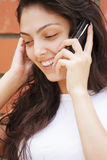 Happy woman in white talking cellphone Royalty Free Stock Image