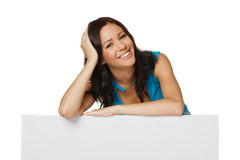 Happy woman with whiteboard. Smiling happy woman standing behind and leaning on a white blank billboard / placard, over white background Stock Image