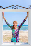 Happy woman in window in front of blue sea and beach Royalty Free Stock Photography