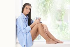 Happy woman on window sill. Happy woman sitting on window sill with coffee mug in morning sunshine, smiling Stock Image