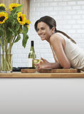 Happy Woman With Wineglass Leaning On Counter Stock Photo
