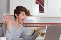 Happy woman winning internet auction game. Or competition with suprised face Royalty Free Stock Photography