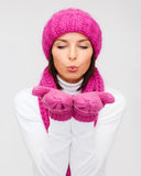 Happy woman in winter clothes blowing on palms Stock Image