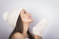 Happy woman in winter clothes blowing on palms Stock Photos