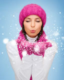 Happy woman in winter clothes blowing on palms Royalty Free Stock Photo