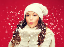 Happy woman in winter clothes blowing on palms Stock Images