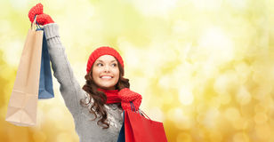 Happy woman in winter clothes with shopping bags. Holidays, christmas, x-mas, sale and people concept - happy young asian woman in winter clothes with shopping Stock Images