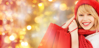 Happy woman in winter clothes with shopping bags. Holidays, christmas, sale and people concept - close up of happy smiling young woman in winter clothes with stock photography