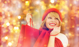 Happy woman in winter clothes with shopping bags. Holidays, christmas, sale and people concept - happy smiling young woman in winter clothes with shopping bags royalty free stock images