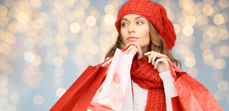 Happy woman in winter clothes with shopping bags. Holidays, christmas, sale and people concept - happy young woman in winter clothes with shopping bags over Stock Photos