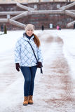 Happy woman in winter clothes standing in front of the Palace staircase Royalty Free Stock Photos