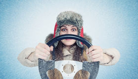 Happy Woman in winter clothes with a steering wheel, snow blizzard. Concept car driver. Stock Photo