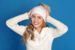 Happy woman in winter clothes under falling snow. On blue background Stock Photos