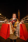 Happy woman in winter coat showing shopping bags while in Venice Stock Image